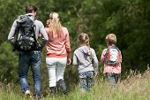 stock photo of 7-year-old  - Rear View Of Family Hiking In Countryside - JPG