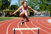 picture of athletic woman  - Athletic girl hurdling at the track clearing the hurdle - JPG