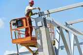 stock photo of assemblage  - worker joiner in uniform and safety protective equipment at metal construction frames installation and assemblage - JPG