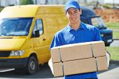 stock photo of in front  - Smiling young male postal delivery courier man in front of cargo van delivering package - JPG