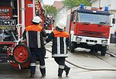 image of fire brigade  - Fireman in uniform operating fire engine or fire truck on duty during training - JPG