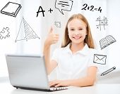 education, school, technology and internet concept - little student girl with laptop pc at school