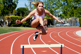 pic of athletic woman  - Athletic girl hurdling at the track clearing the hurdle - JPG