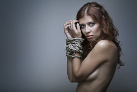 foto of sadism  - redhaired woman bondage on gray background - JPG