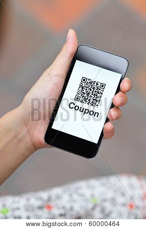 QR coupon on mobile display holding by woman hand