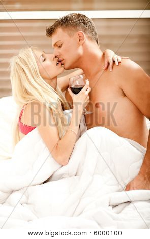 Young Couple Making Love In Bedroom