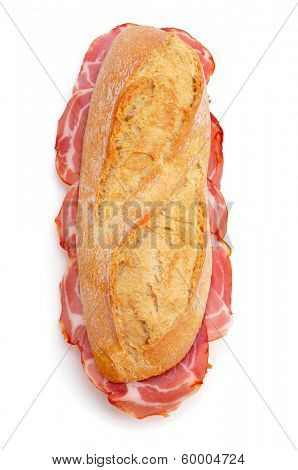 closeup of a spanish bocadillo de lomo embuchado, a sandwich with cold meats of pork, on a white background