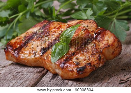 Juicy Piece Of Grilled Meat With Basil On An Old Wooden