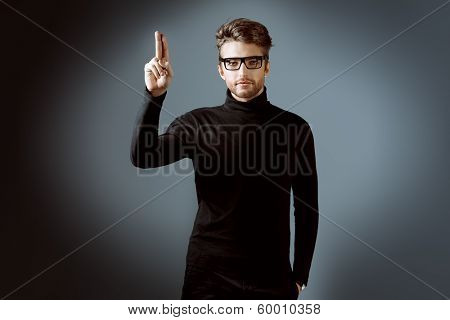 Imposing man in elegant black clothes and glasses posing over dark background.