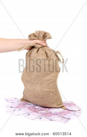 Hand holds bag with money.