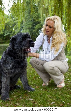 A young blond woman with her pet dog in the park