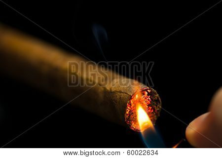 lighting up a cigar, black background