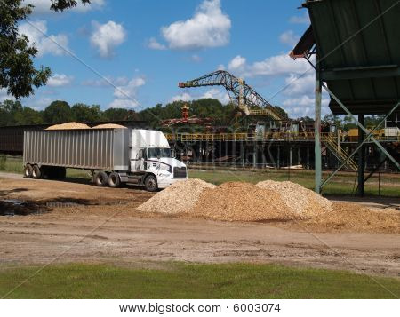 Semi Truck Loaded With Wood Chips and a Logging Crane