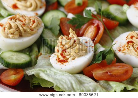 Homemade deviled eggs served on a salad of miniature tomatoes, lettuce, sliced cucumber and chopped green onion scallions, side view