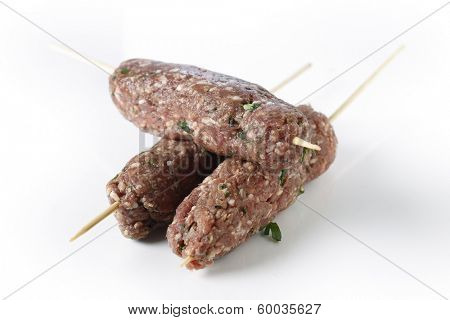 Lamb kofta skewers over a white background