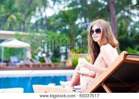Happy young woman in bikini laying on chaise-longue drinking coffee