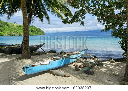 A blue polynesian outrigger that's still used today rests on the shore of a tropical island in Fiji