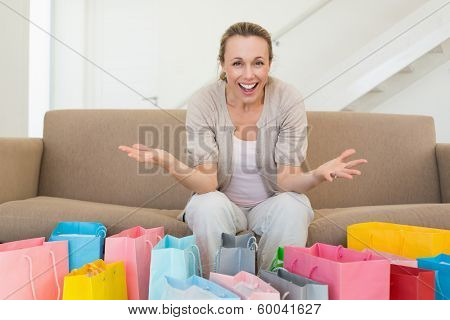 Excited woman looking at camera with many shopping bags at home in the living room