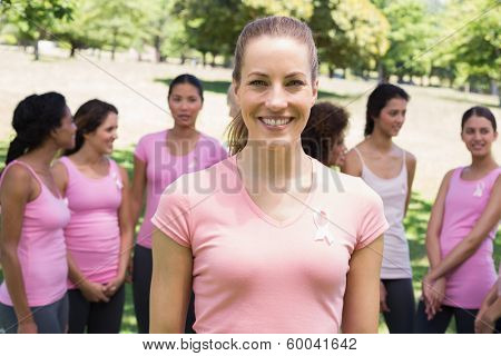 Portrait of smiling woman with volunteers in background during breast cancer awareness at park