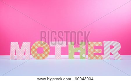 Mother- lettering of handmade paper letters on pink background