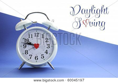 Retro Vintage Style White Alarm Clock On Blue And White Background With Daylight Saving Sample Text