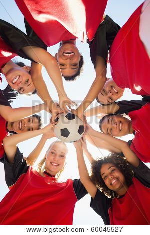 Directly below shot of female soccer team with ball forming huddle against clear sky