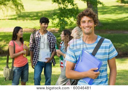 Portrait of a boy with happy college friends in background at the campus