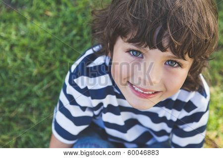 Close-up portrait of a cute young boy smiling at the park