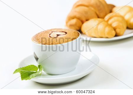 Close up view of cup of coffee with heart ornament