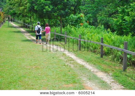 Old Couple Walking A Long Stretch Of Road