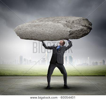 Powerful businessman holding huge stone above head