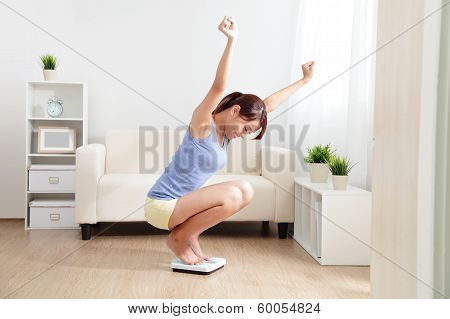 Happy Woman Smiling On Weighing Scales