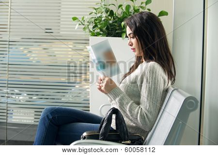 young woman reading brochure in doctor's waiting room
