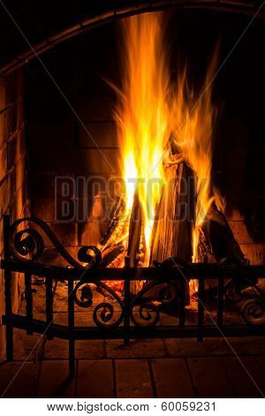 Home Fire Burning In Brick Fireplace. Seasonal And Holiday Fire, Closeup