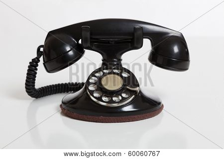 A black, vintage rotary phone on a white background