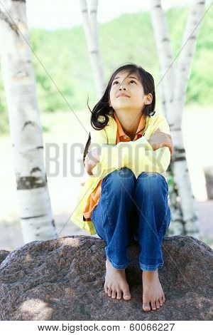 Young Biracial Girl Sitting On Rock Under Trees