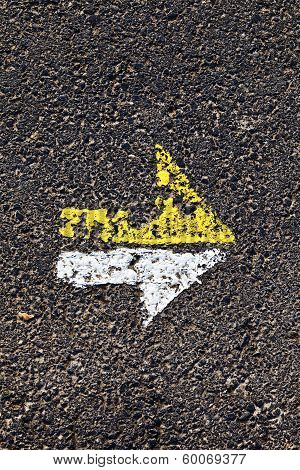 Arrow In Yellow And White On A Paveway For Orientation