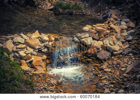 waterfall created to artificially with herbs near the Carpathians