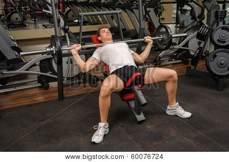 Handsome young man doing Barbell Incline Bench Press workout in gym