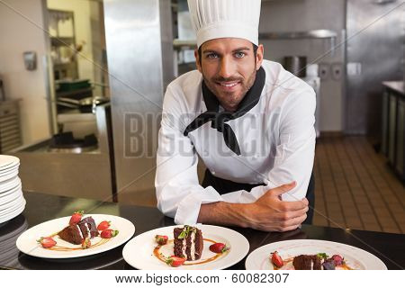 Happy chef looking at camera behind counter of desserts in a commercial kitchen