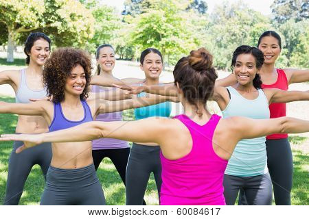 Happy women exercising with female instructor at park
