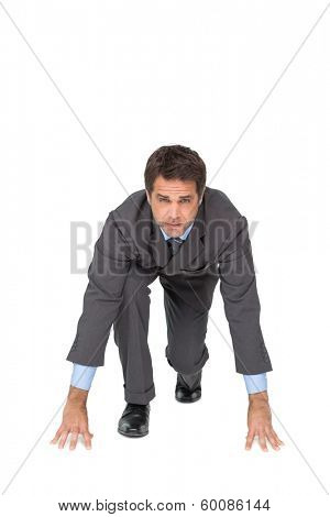 Focused businessman ready to race on white background