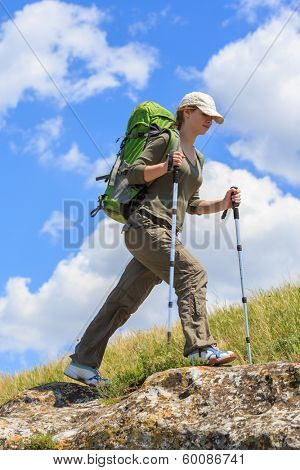 Young tourist woman with backpack and trekking poles walking on the mountain path