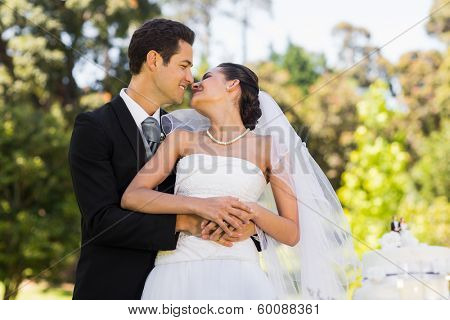 Happy young newlywed couple about to kiss besides wedding cake at the park