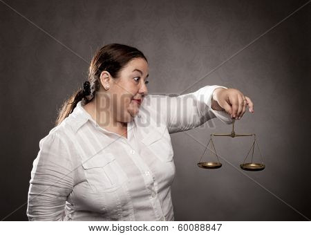 fat woman holding a scale on a gray background