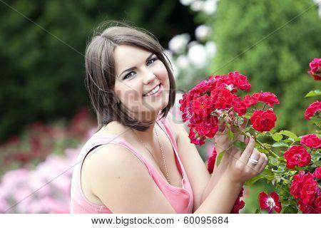 Beautiful Girl In Summer Garden Near Blooming Rosebush