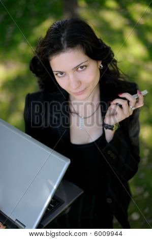 Young Lady Outside  With A Laptop And A Cell Phone