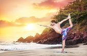 stock photo of natarajasana  - Yoga by man on the beach near the ocean at sunset in India - JPG