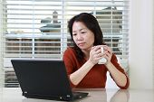 pic of telecommuting  - An asian woman working from home with a cup of coffee - JPG