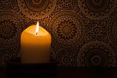 image of altar  - A candlelight burning in front of vintage wallpaper - JPG